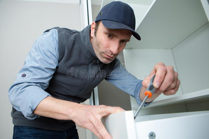 Workman fixing kitchen drawer with screwdriver royalty free stock photos