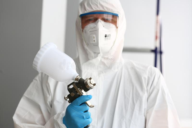 Workman hold in arm airbrush gun wearing protective suit stock photos