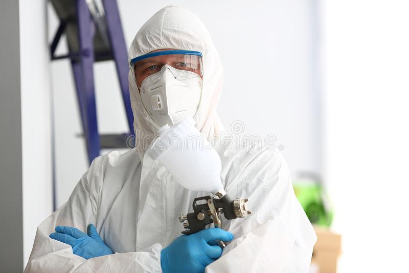 Workman hold in arm airbrush gun wearing protective suit royalty free stock photos