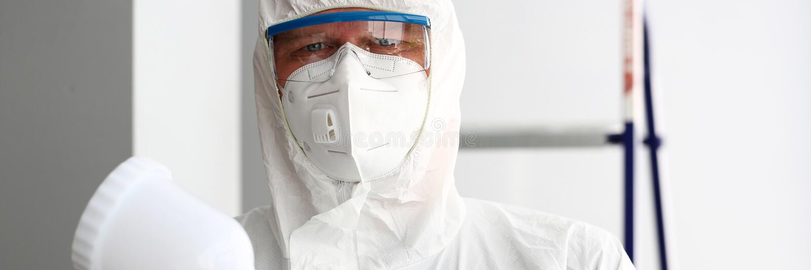 Workman hold in arm airbrush gun wearing protective suit royalty free stock photography
