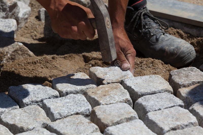 Workman laying cobbles stock photography