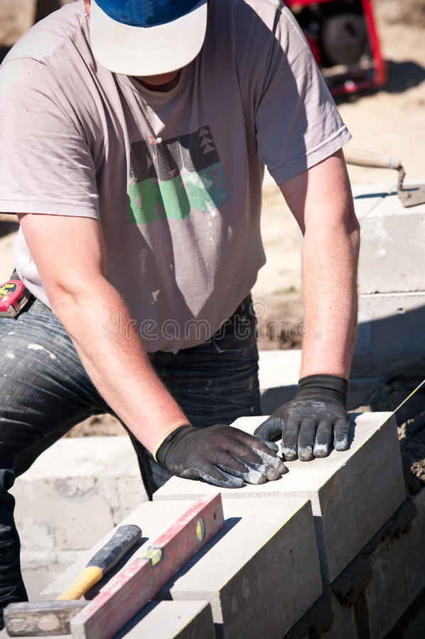 Workman laying concrete blocks. At a construction site royalty free stock photos