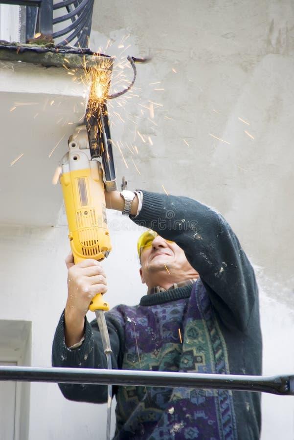 Workman med den elektriska sawen arkivbild