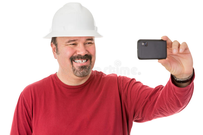 Workman posing for a self-portrait. Workman with a neat goatee beard weaning a hardhat posing for a self-portrait giving a cheesy grin as he looks into the stock photos