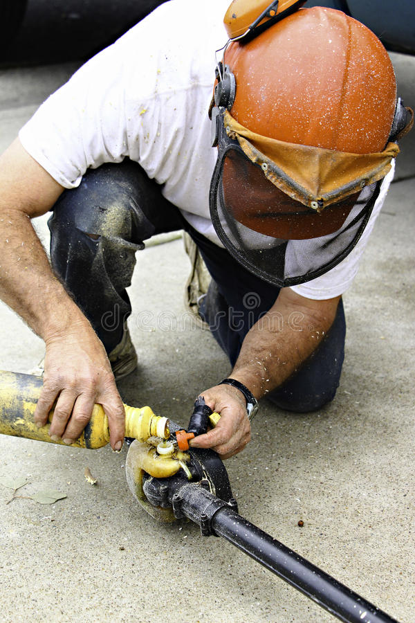 Workman pouring fuel in a chainsaw stock images
