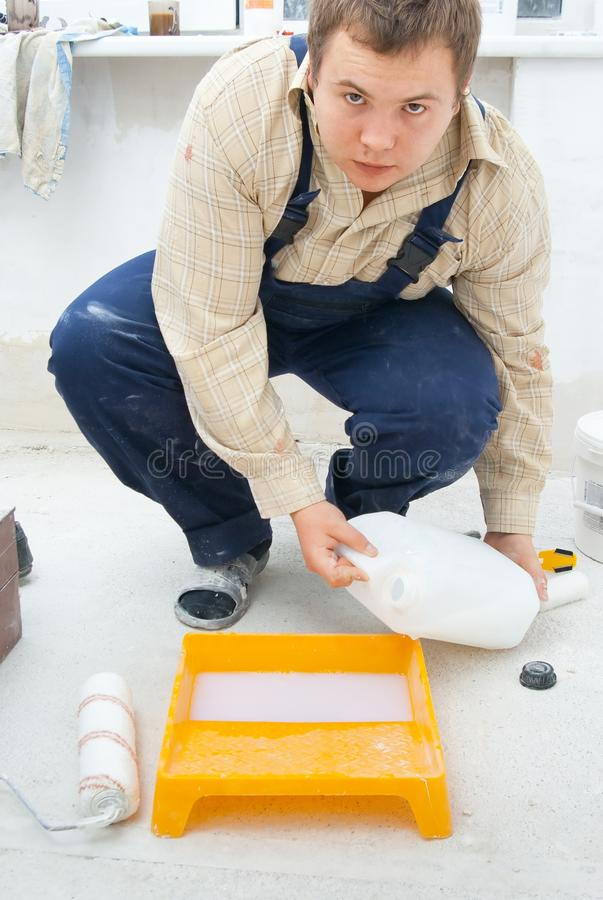 Workman pouring paint stock image
