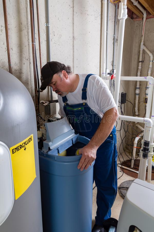 Workman replacing an old domestic water softener. Looking into problems encountered when installing the new tank in a utility room stock image