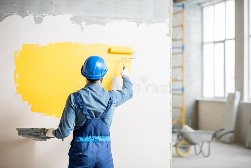 Workamn painting wall indoors. Workman in uniform painting wall with yellow paint at the construction site indoors stock images