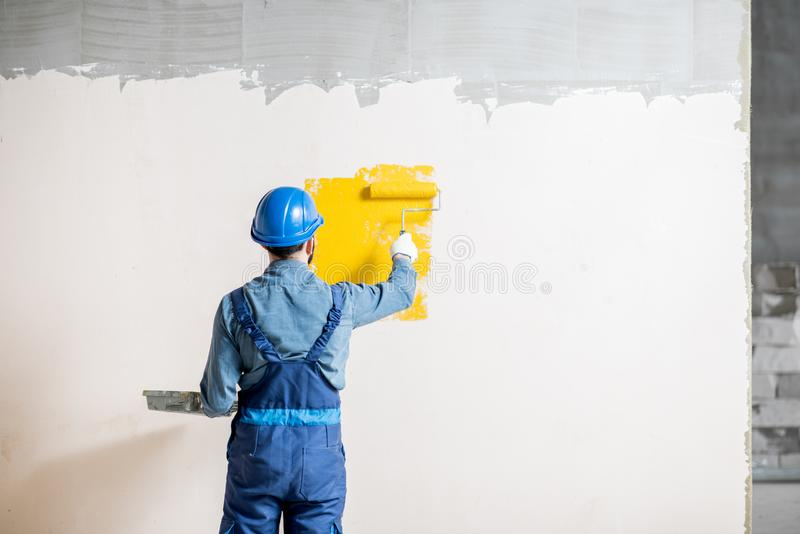 Workman painting wall indoors. Workman in uniform painting wall with yellow paint at the construction site indoors royalty free stock images