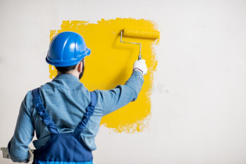 Workman painting wall indoors. Workman in uniform painting wall with yellow paint at the construction site indoors stock photography