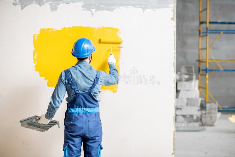 Workman painting wall indoors royalty free stock images
