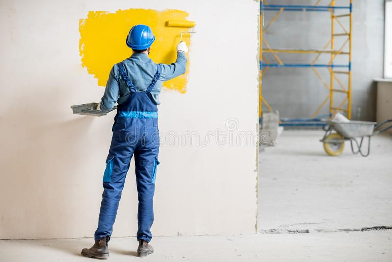 Workman painting wall indoors. Workman in uniform painting wall with yellow paint at the construction site indoors royalty free stock photo