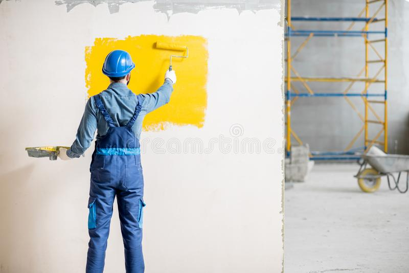 Workman painting wall indoors. Workman in uniform painting wall with yellow paint at the construction site indoors royalty free stock image
