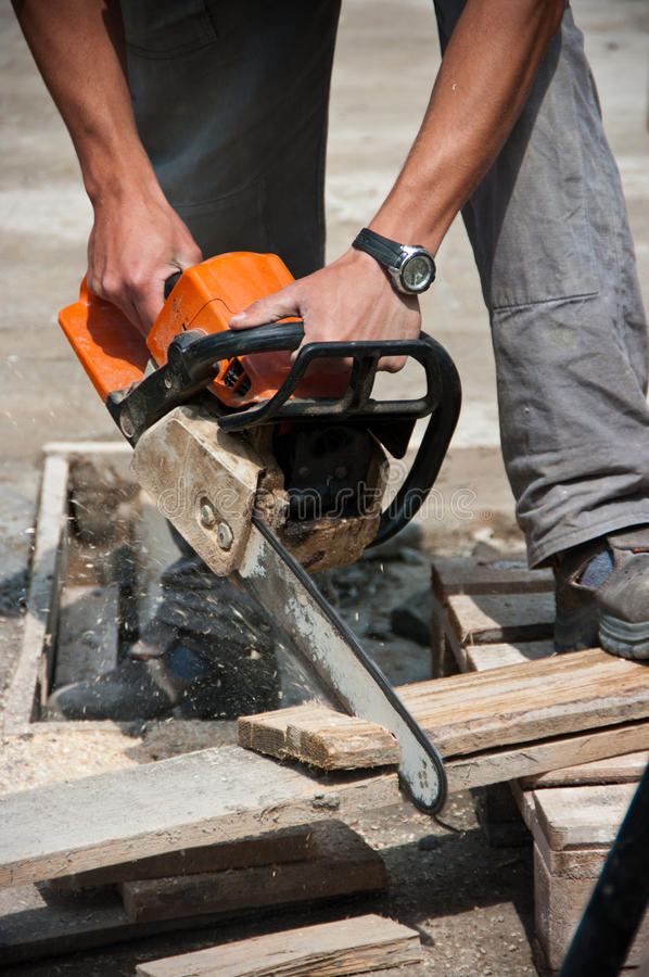 Workman using chainsaw royalty free stock image