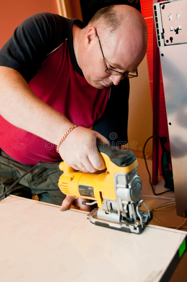 Workman using jigsaw. Half body portrait of middle aged workman using power or jigsaw on piece of wood royalty free stock image