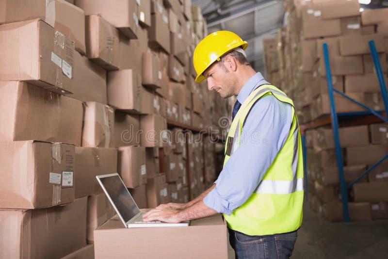 Workman using laptop at warehouse royalty free stock images
