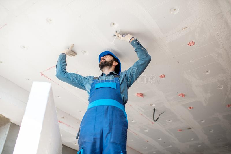 Workman warming the building. Builder warming building ceiling mounting foam panels on the construction site royalty free stock images