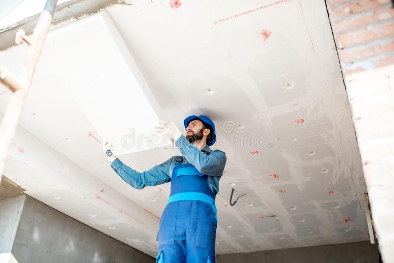 Workman warming the building. Builder warming building ceiling mounting foam panels on the construction site royalty free stock photography
