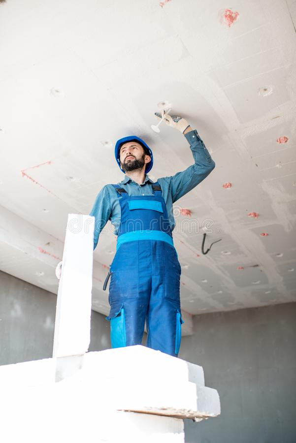 Workman warming the building. Builder warming building ceiling mounting foam panels on the construction site stock images