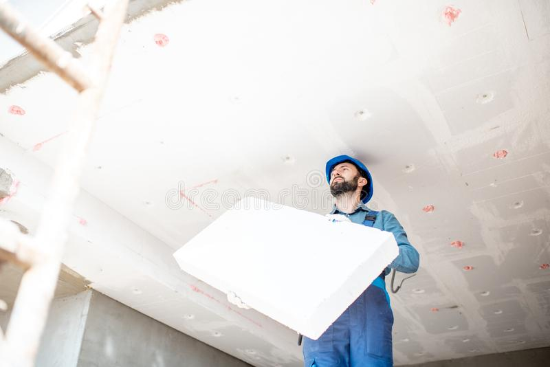 Workman warming the building. Builder warming building ceiling mounting foam panels on the construction site stock image