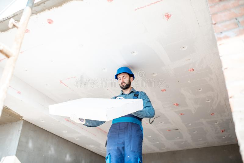 Workman warming the building. Builder warming building ceiling mounting foam panels on the construction site stock photography