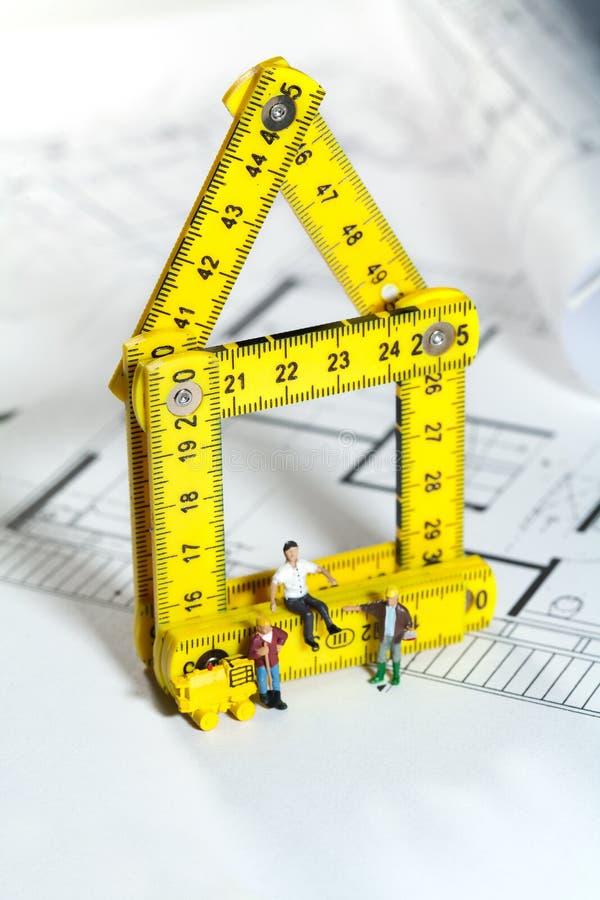 Workmen on a blueprint building site. Conceptual image of tiny miniature workmen on a blueprint building site stock images