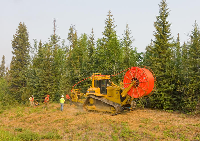 Workmen laying fibre optic cable in the northwest territories royalty free stock images