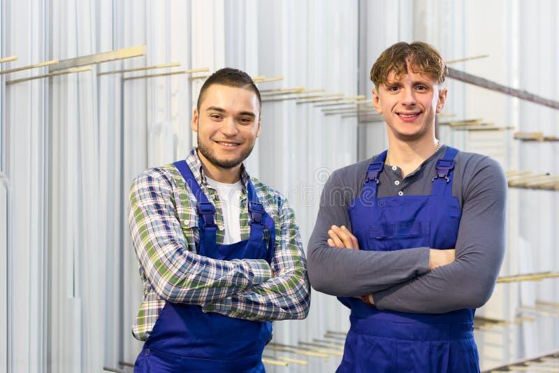 Workmen near PVC window frames at factory stock image