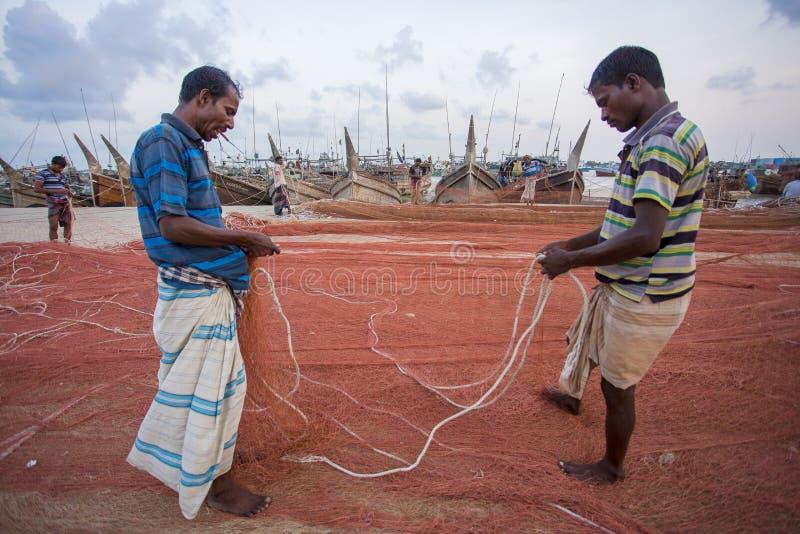 Workng dei pescatori sulla spiaggia di sabbia fra le loro barche e reti, Bangladesh fotografia stock
