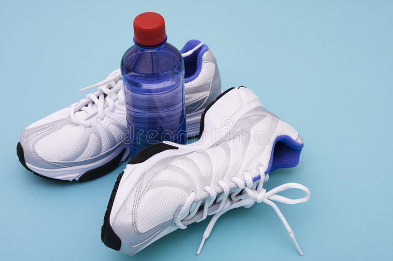 Workout. Sneakers with water bottle on blue background royalty free stock photos