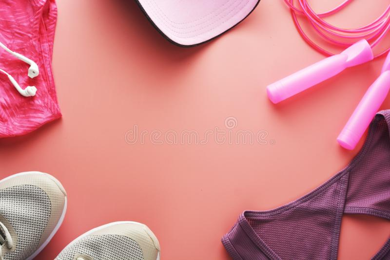 Workout concept, flat lay with copy space. Sport shoes, jumping rope, yoga clothes over pink background. Health, running workout,. Fitness and yoga concept royalty free stock images