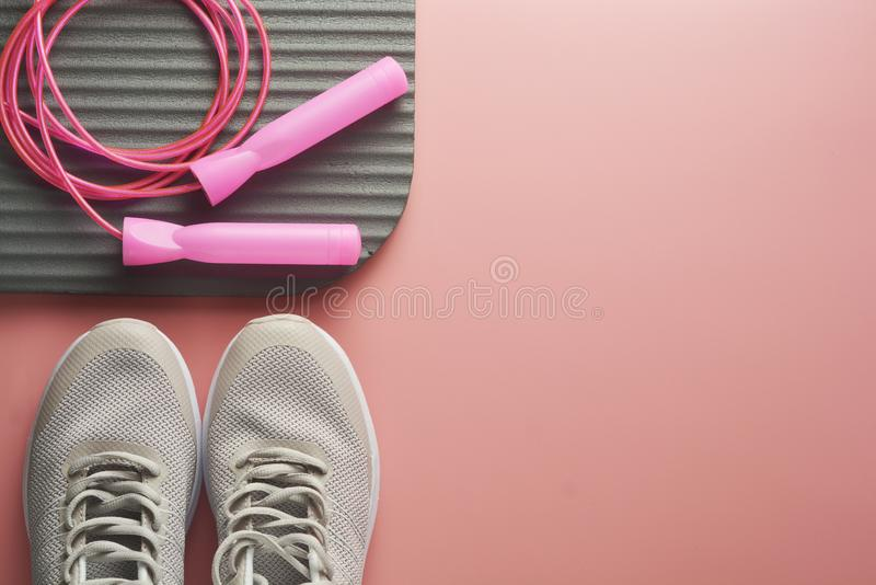 Workout concept, flat lay with copy space. Sport shoes, jumping rope, yoga clothes over pink background. Health, running workout,. Fitness and yoga concept royalty free stock photography