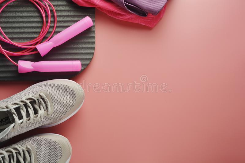 Workout concept, flat lay with copy space. Sport shoes, jumping rope, yoga clothes over pink background. Health, running workout,. Fitness and yoga concept royalty free stock photos