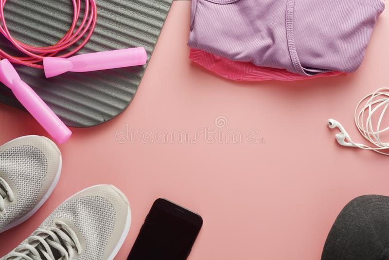 Workout concept, flat lay with copy space. Sport shoes, jumping rope, yoga clothes over pink background. Health, running workout,. Fitness and yoga concept stock images