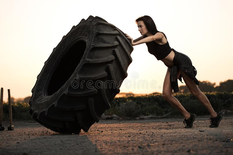 Workout fitness concept. Sports woman turns over tire wheel in gym, sweat drops, force royalty free stock images