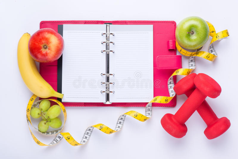 Workout and fitness dieting copy space diary. Healthy lifestyle concept. Apple, dumbbell, and measuring tape on rustic wooden royalty free stock image