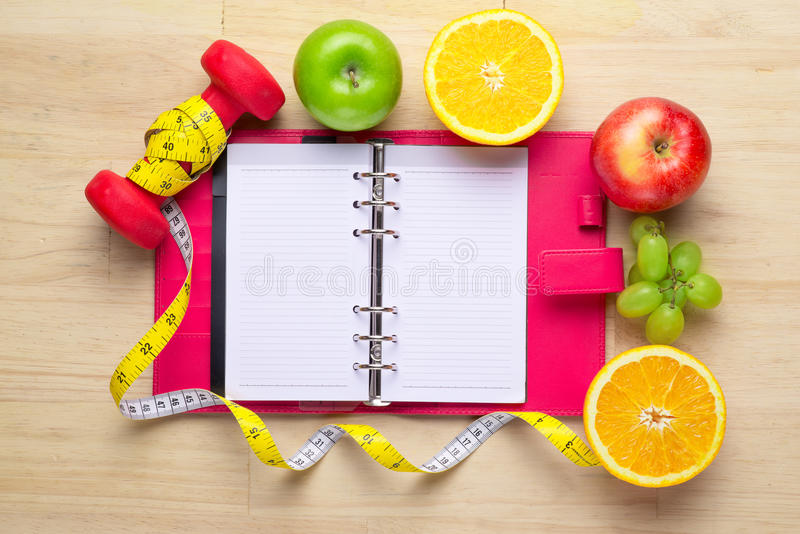 Workout and fitness dieting copy space diary. Healthy lifestyle concept. Apple, dumbbell, and measuring tape on rustic wooden royalty free stock photography