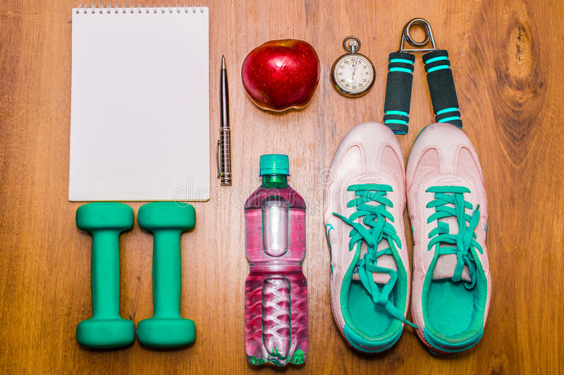 Workout and fitness dieting copy space diary. Healthy lifestyle concept. Dumbbell, water, expander hand ball on rustic stock images