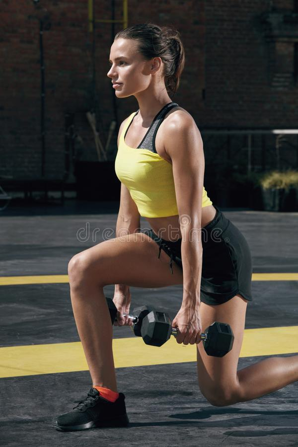 Workout. Fitness woman doing leg exercise with dumbbell outdoors royalty free stock image