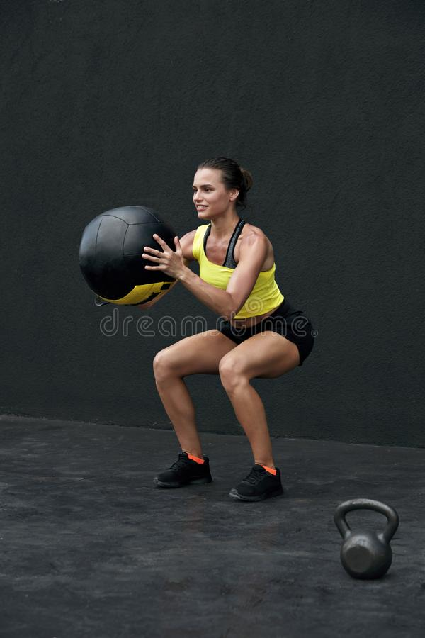 Workout. Fitness woman doing squat exercise with med ball. Sport. Workout. Fitness woman doing squat exercise with med ball at gym. Sport female model in royalty free stock image