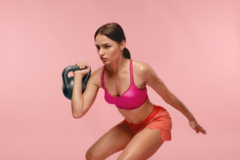 workout Frauen-Training mit Dummkopf auf rosa Hintergrund lizenzfreie stockbilder