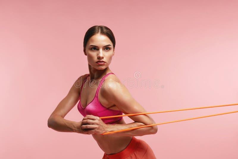 workout Frauen-Training mit Widerstand-Bändern auf rosa Hintergrund stockfotografie