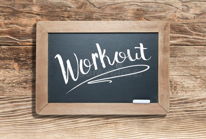 Workout Written on Slate Chalk Board Against Aged Wood Background. Workout Hand Written on Slate Chalk Board Against Aged Wood Background royalty free stock image