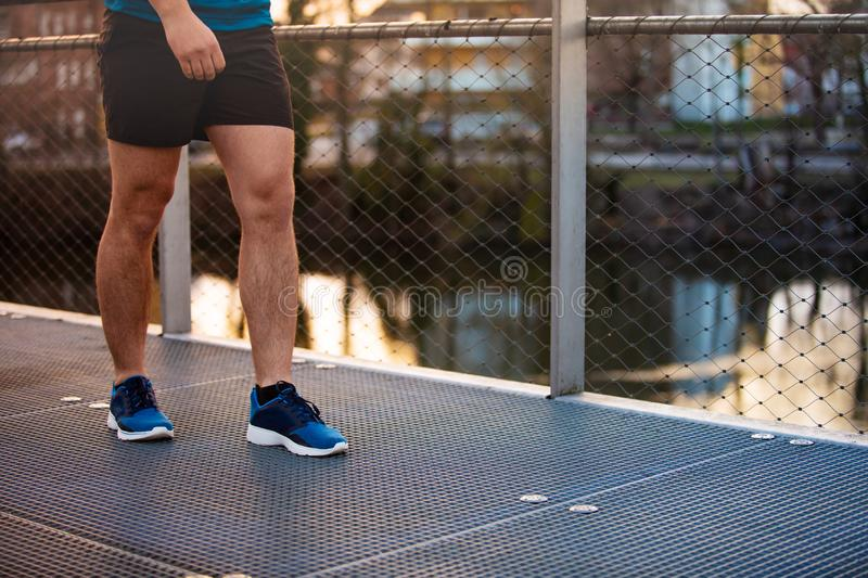 Workout jogging activity. Young man sporty legs running outdoor along a bridge in the morning. Self overcome conquering obstacles and win. Healthy lifestyle royalty free stock image