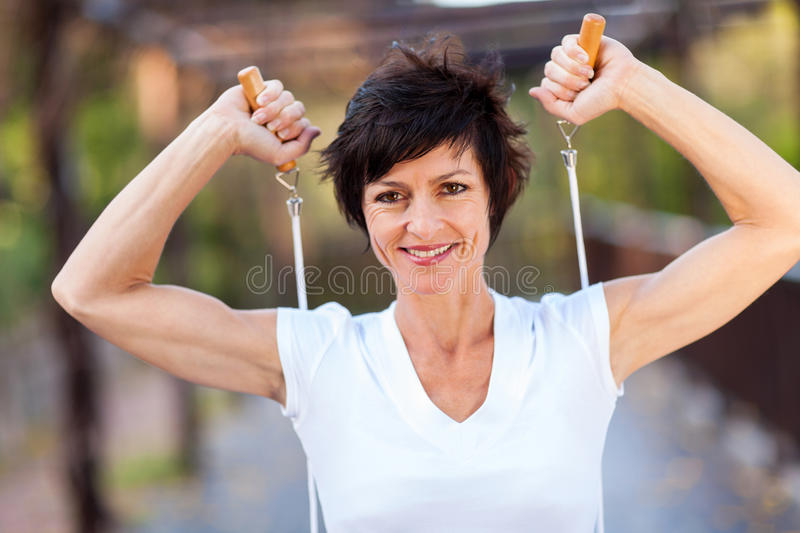 Workout with jumping rope. Happy middle aged woman workout with jumping rope royalty free stock images