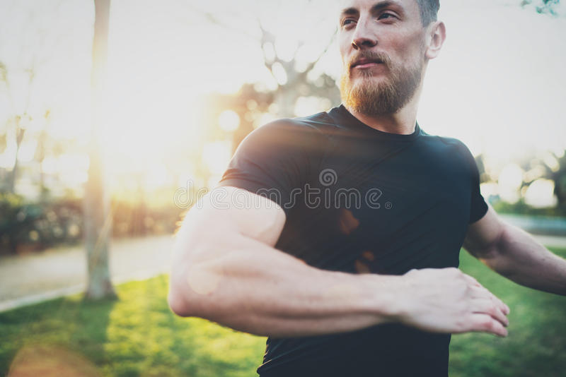 Workout lifestyle concept.Young man stretching his arm muscles before training.Muscular athlete exercising outside in stock photography