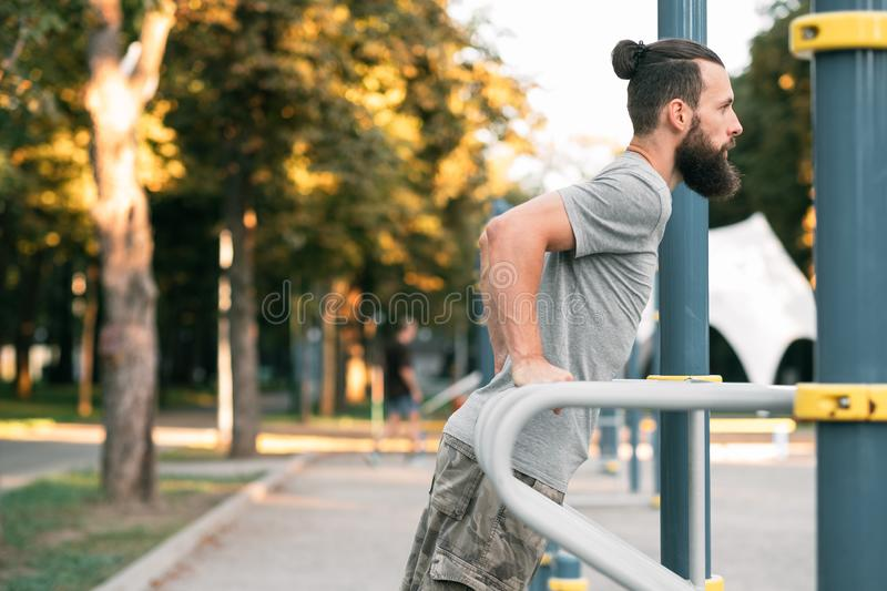 Workout outdoor training man bar dips fitness. Workout and outdoor training. man doing parallel bar dips. fitness and healthy lifestyle royalty free stock photo