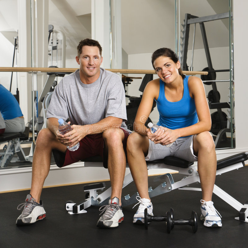 Workout partners. Man and woman sitting on exercise machine smiling holding water bottles