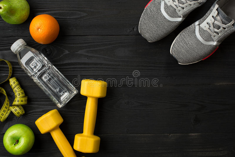 Workout plan with fitness food and equipment on dark background, top view. Workout plan with fitness food and sport equipment on dark background, top view. Copy stock photography