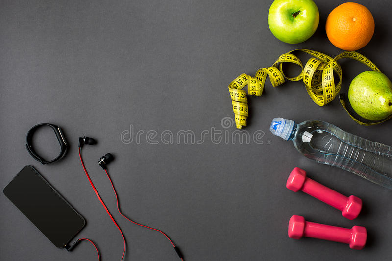 Workout plan with fitness food and equipment on gray background, top view. Workout plan with fitness food and sport equipment on gray background, top view. Copy royalty free stock photography